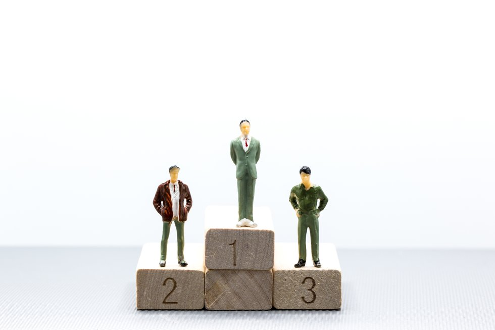 Miniature people: small figures businessmen stand on wooden podium using as background business team competition concept.