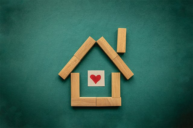 House made of wooden blocks with a red heart inside on a blue ba